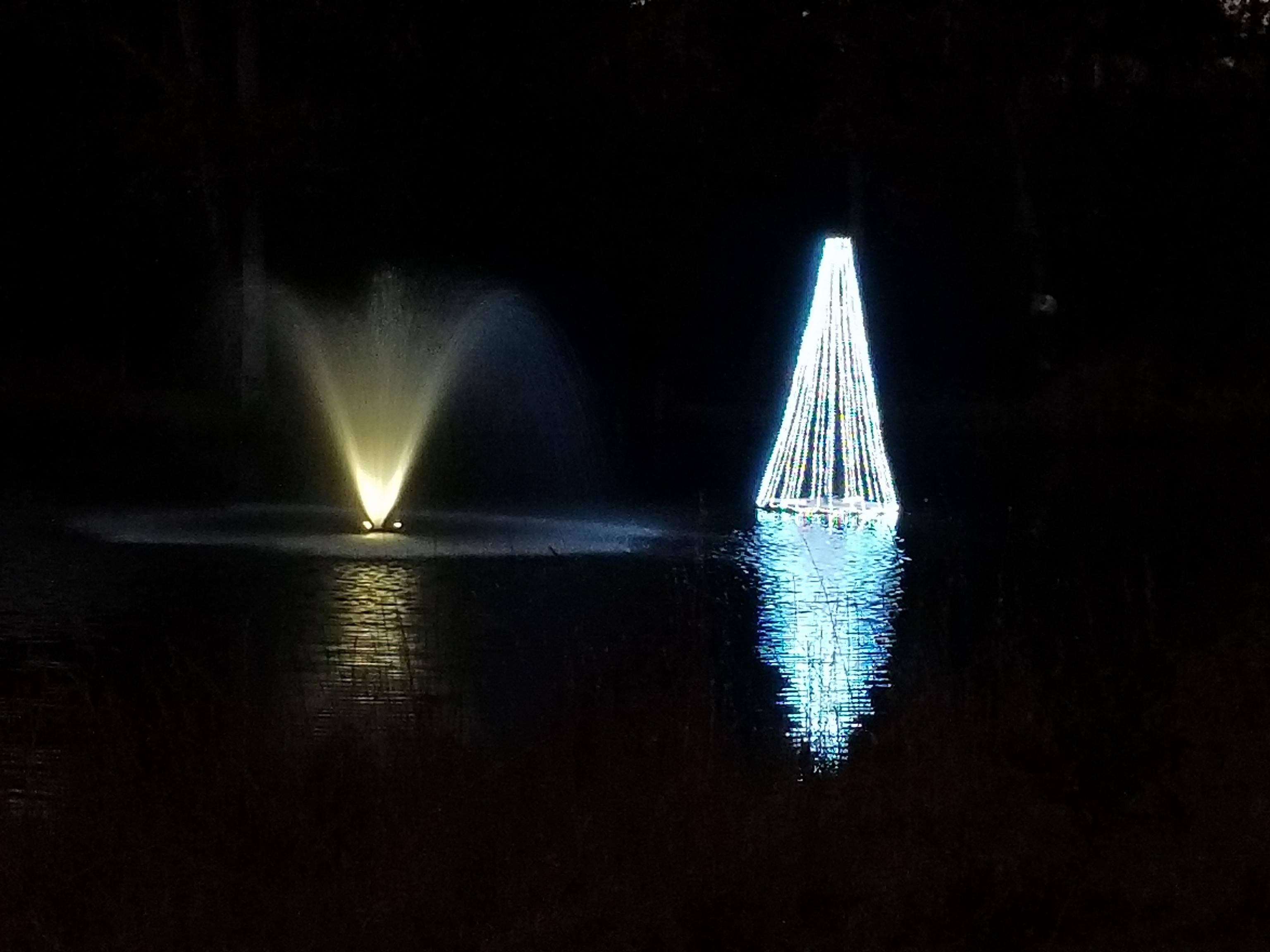 3 christmas trees in a lake floating tree and fountain in a lake